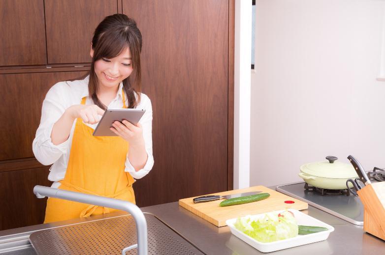 料理前にアイパッドで調べる女性